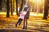 Mom Is Spinning Daughter In Autumn Colorful Park On Sunny Day. Mother And Daughter Playing Circling poster