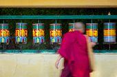 Buddhist monk (llama) rotating prayer wheels on kora