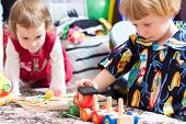 Bonitos crianças brincando no jardim de infância com brinquedos coloridos