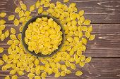 Lot Of Whole Raw Yellow Pasta Conchiglie Variety In A Grey Ceramic Bowl Flatlay On Brown Wood poster