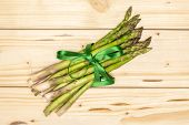 Bundle Of Lot Of Whole Fresh Green Asparagus Spear Tied By Green Ribbon Flatlay On Natural Wood poster