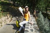 Young Traveler Tourist Woman In Yellow Clothes Hat With Suitcase City Map Looking Aside Sitting On S poster