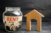 Glass Jar With Coins And The Inscription rent And A Small Wooden House. Rental Of Property, Apartm poster
