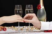 man putting engagement ring on the finger of a woman, happy couple celebrating with Champagne