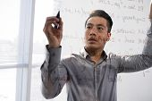 Young Asian Man Writing Script On Glass Transparent Board Standing Behind It poster