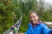 Canada travel tourist woman taking selfie photo at Capilano Suspension Bridge in Vancouver, British  poster