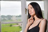Young beautiful woman dream of something at her mansion house near window.