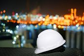 White Safety Helmet On Blurred Lights Industrial Plant Background, Worker At Night Concept In Petroc poster