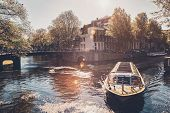 Amsterdam canal with tourist boat and old houses on sunset. Amsterda, Netherlands poster