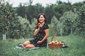Happy Healthy Pregnancy. Portrait Of Pregnant Young Brunette Caucasian Woman Sitting On Grass Eating poster