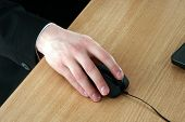 Man's Hand Holds A Computer Mouse On A Desk