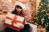 Christmas Girl Kid In A Santa Hat Opening Mouth. Cute Child Open Gift Box With Red Ribbon At Home. D poster