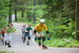 picture of inline skating  - Group of men and women on rollerblades skating at park - JPG