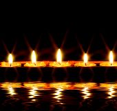 stock photo of condolence  - row of candles reflected in the water - JPG