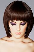 closeup portrait of beautiful young woman with short brown hair and dramatic eye makeup of purple ey