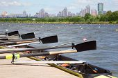 Long sport boat with oars stands at wooden pier at background of urban landscape. Focus on oars.