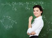 Smiley teacher hands chalk standing at the blackboard where the chemical formula is written