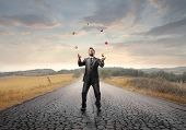 stock photo of juggler  - Young businessman juggling on a country road - JPG