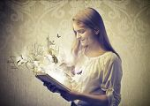 foto of working animal  - Smiling teenage girl reading a book with birds coming out from it - JPG