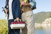 Midsection of a grandfather with teenage boy holding fishing rod and picnic box
