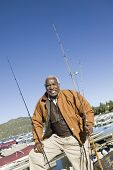 Portrait of happy African American man standing with fishing rods with boats in background