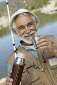 Portrait of a happy senior man having coffee from a thermos flask while fishing