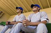 Low angle view of players watching the game intensely while sitting in dugout