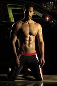 Sexy portrait of young fit shirtless man at night