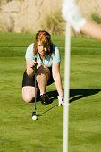 Mulher agacha-se e alinha sua tacada em um campo de golfe