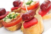 closeup of a plate with different spanish pinchos, like those made with chorizos an red pepper, or tomato and cheese