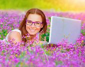 Closeup on cute teen girl wearing glasses lying down on pink floral meadow with laptop, modern techn