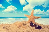 Starfish on beach with sunglasses against a lovely summer sky - vintage feel