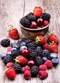 stock photo of berries  - tasty summer fruits on a wooden table. Cherry Blue berries strawberry raspberries Blackberries pomegranate