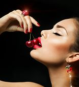 Sexy Woman Eating Cherry. Sensual Red Lips. Red Manicure, Lipstick and Ring. Desire. Sexy red Lips w