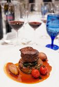Red wines and tenderloin steak on restaurant table