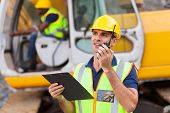 stock photo of heavy equipment operator  - construction foreman talking on walkie - JPG