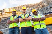 stock photo of ppe  - group of quarry workers standing next to excavator with arms crossed - JPG