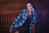 Portrait of a Pretty Mixed Race Young Adult Woman Sitting on Wooden Bench Against a Lustrous Wood Wa