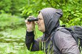 Man with binoculars watching birds at the lake