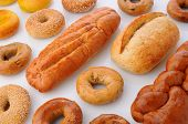 A large group of breads and bagels viewed for overhead on white with reflection. Items include: sesame seed bagels, french breaad, italian bread, baguette and more.Horizontal format fills the frame.