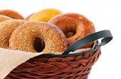 Closeup of assorted fresh bagels in a basket, including egg, sesame seed, multi-grain, plain, and ci