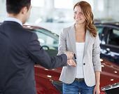 Image of car dealer giving key from car to happy female in automobile center
