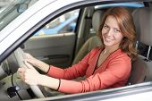 Photo of cute woman sitting in a new car and looking at camera