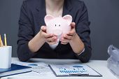 Image of pink piggy bank in human hands