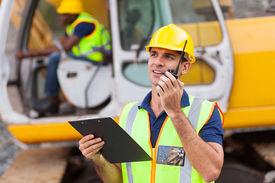 foto of ppe  - construction foreman talking on walkie - JPG