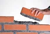 Constructor hand holding a brick and building a wall.