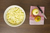picture of partially clothed  - Freshly peeled and sliced apples sit ready prepared in a bowl of cold water while a partially peeled apple is ready to be chopped - JPG