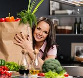 Young woman with grocery bag full of fresh vegetables on a modern kitchen