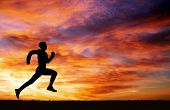 picture of fiery  - Silhouette of running man against the colorful sky - JPG