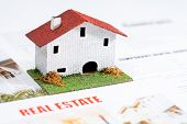 Small Toy House On Real Estate Documents.